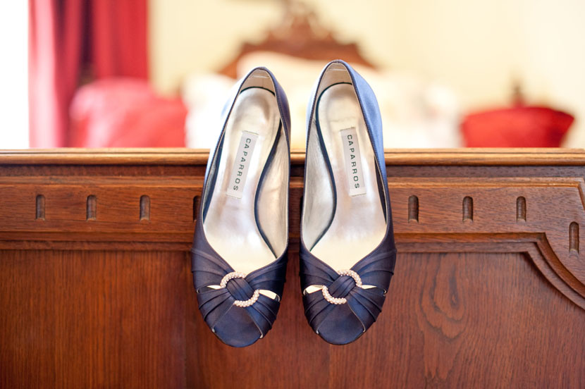 blue wedding shoes perched on bed edge