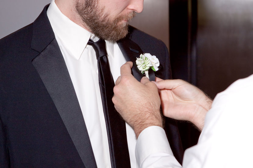 groom applying boutonniere austin wedding photography
