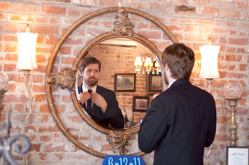 groom checks reflection in mirror austin wedding photographer
