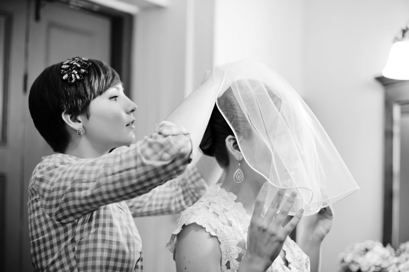 sister helping bride with veil wedding day