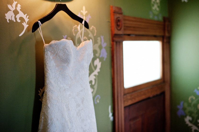 wedding dress on a hanger leading lines doorway green