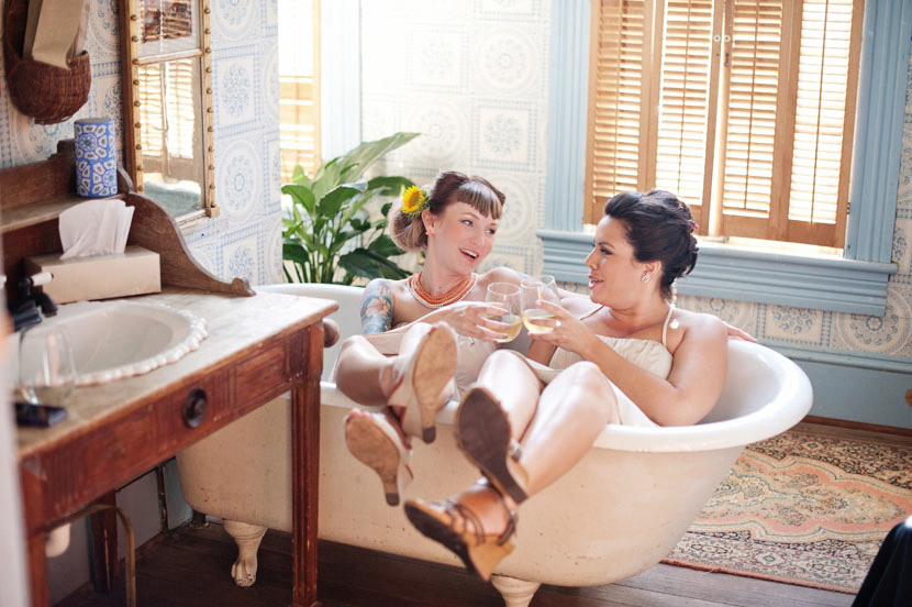 bridesmaids drinking wine in a bathtub