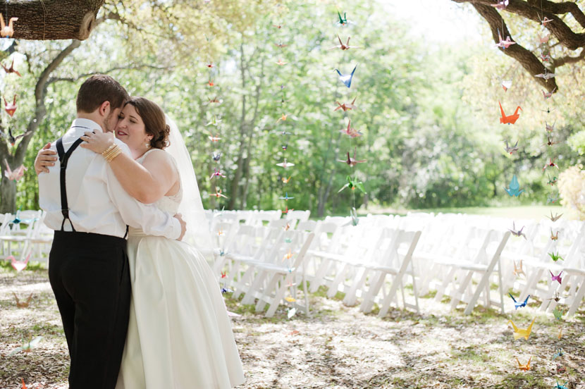 wedding couple hug after first look under crane-decorated trees