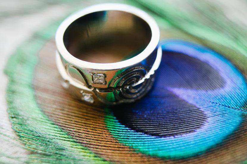 macro wedding ring shot on peacock feathers