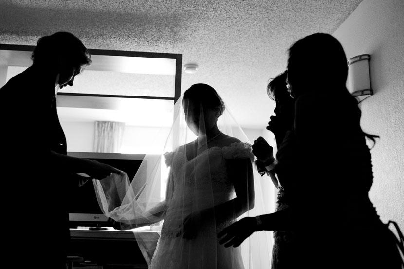 wedding veil being put on the bride