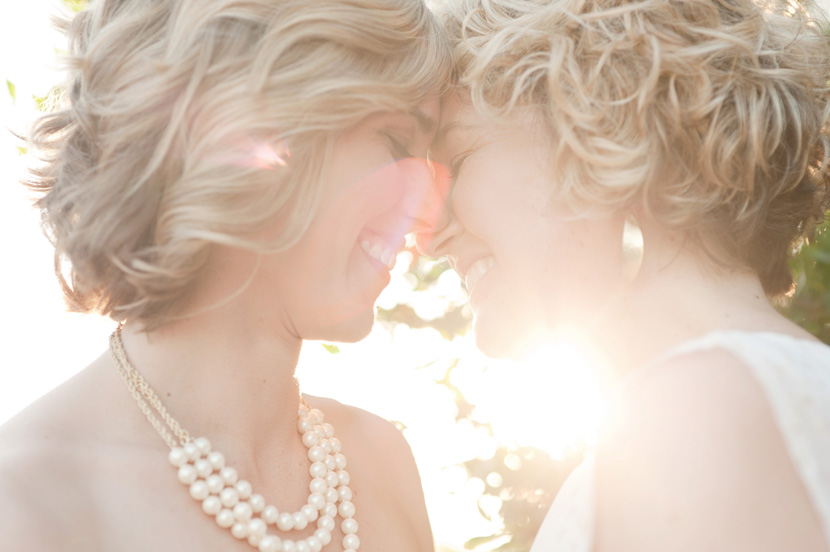 brides touch foreheads in beautiful sunlight