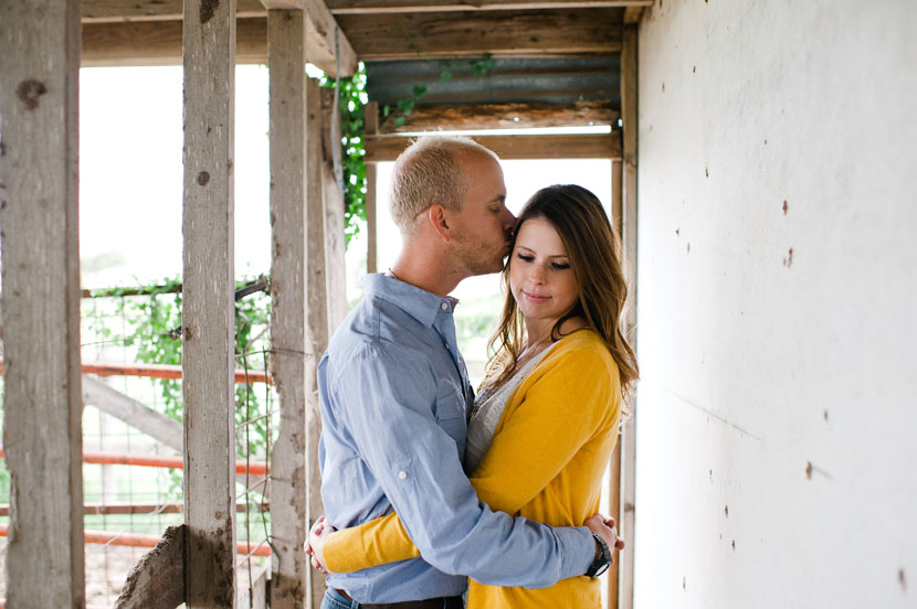 couple snuggles in a barn engagement session