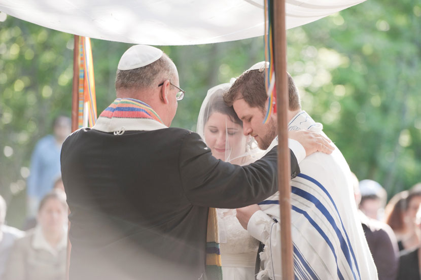 couple embraces rabbi during jewish ceremony