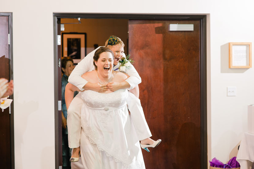 brides piggyback into their wedding reception