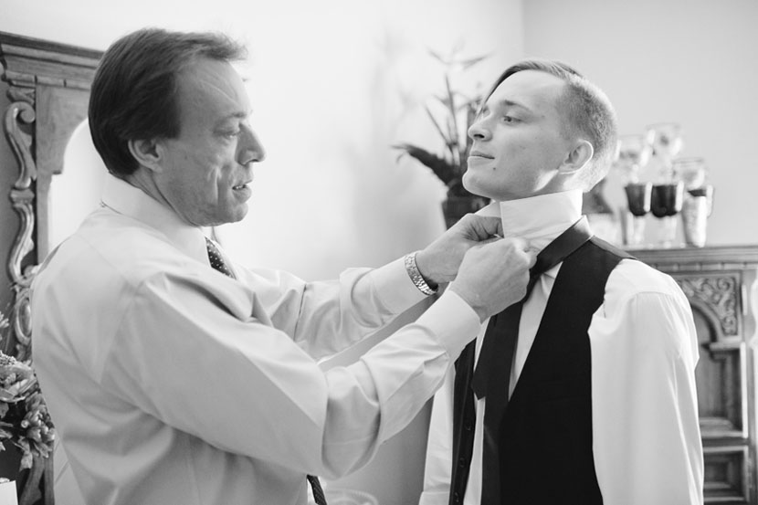 groom ties tie with father