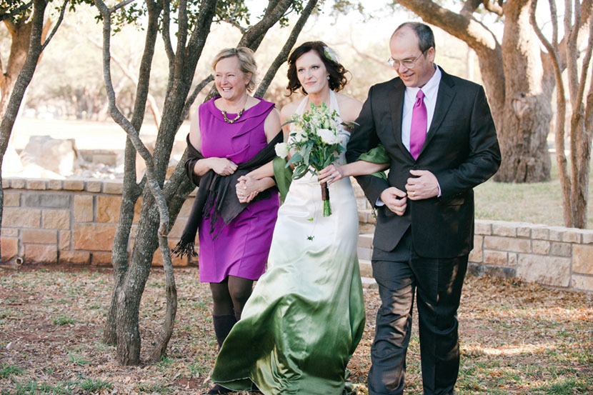 bride walks with both parents