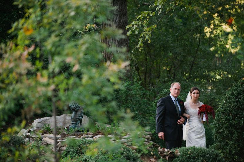 father walks bride down green aisle