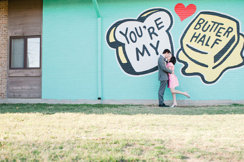 engagement kiss in front of the butter half sign
