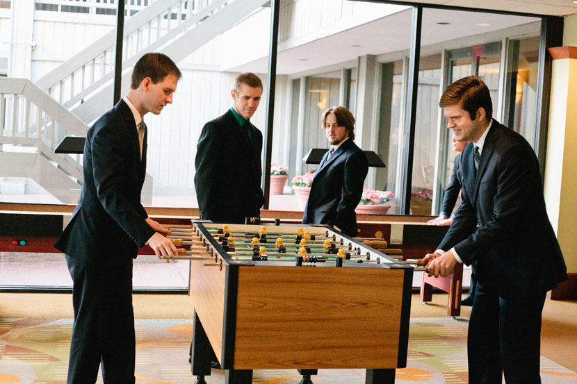 groom playing foosball with groomsmen