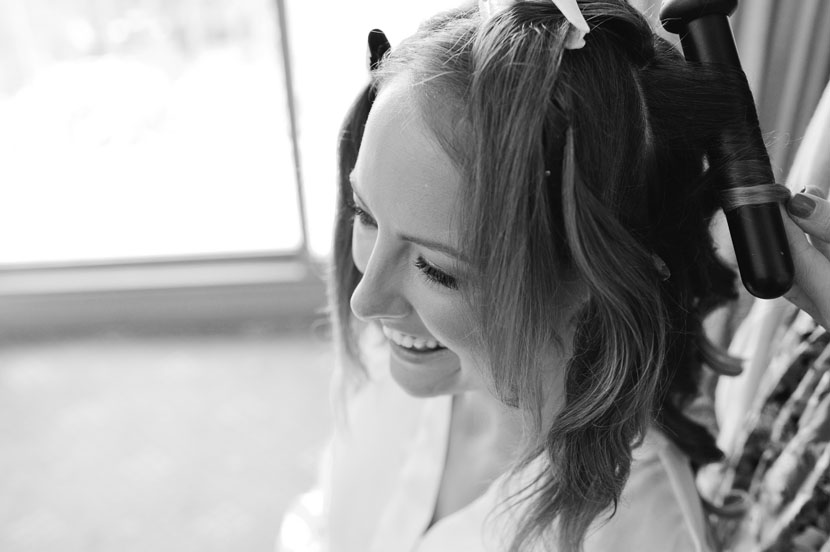 bride getting hair done by stylist on wedding day
