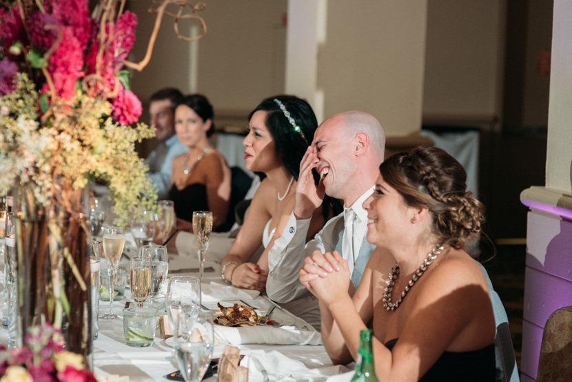 couples laughing during wedding toasts