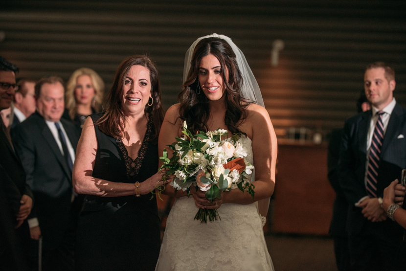 bride and mom walk down the aisle