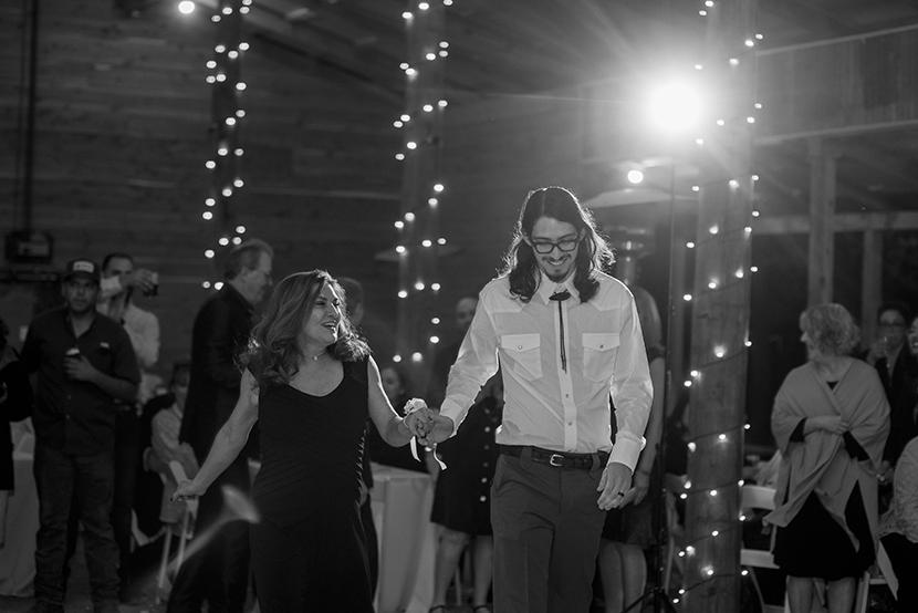 happy mom leading the groom onto the dance floor