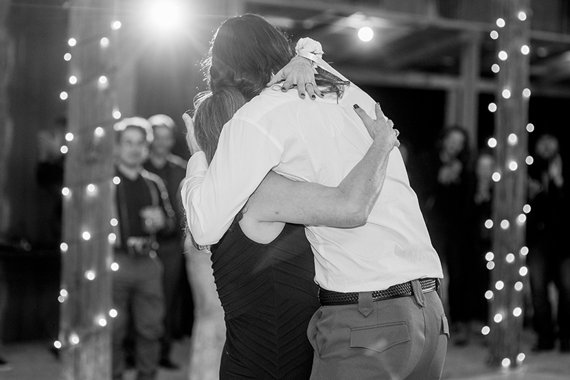 groom embraces mother after mother son dance