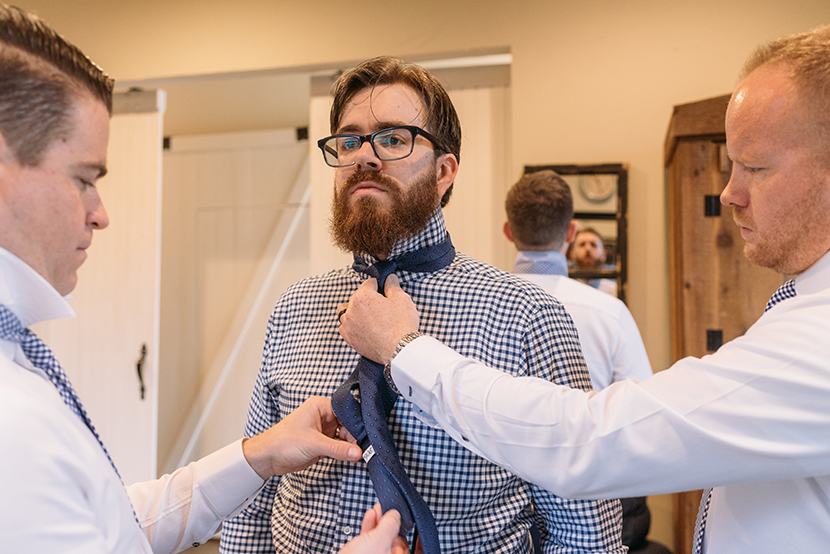 groomsmen help the groom with his tie