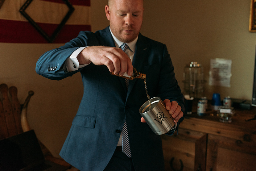 groomsman pours a drink before the festivities