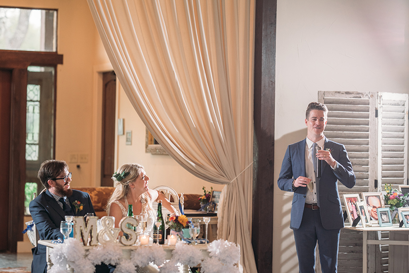 best man gives a speech while the couple laughs