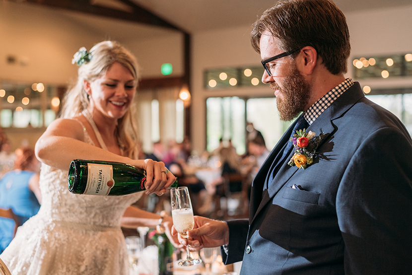 bride pours champagne for groom