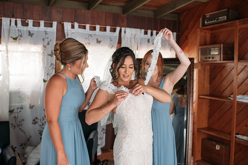 Bridesmaids help bride with dress