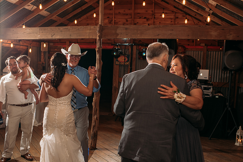 Parents dancing with children during wedding reception
