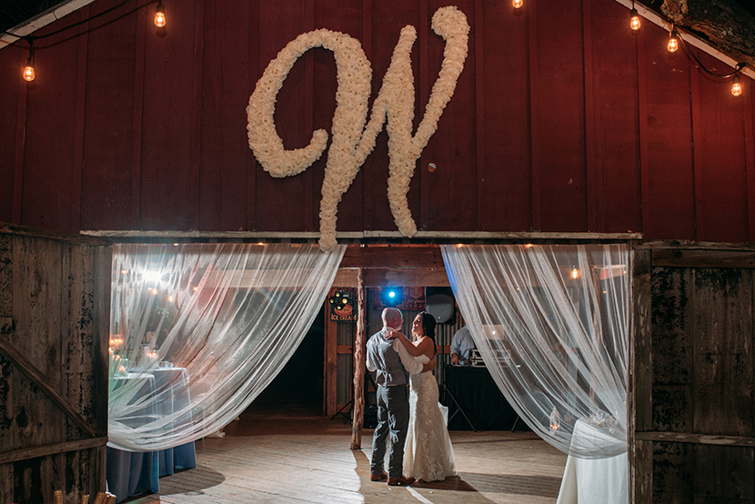 Couple dances under a floral monogram installed on their wedding barn