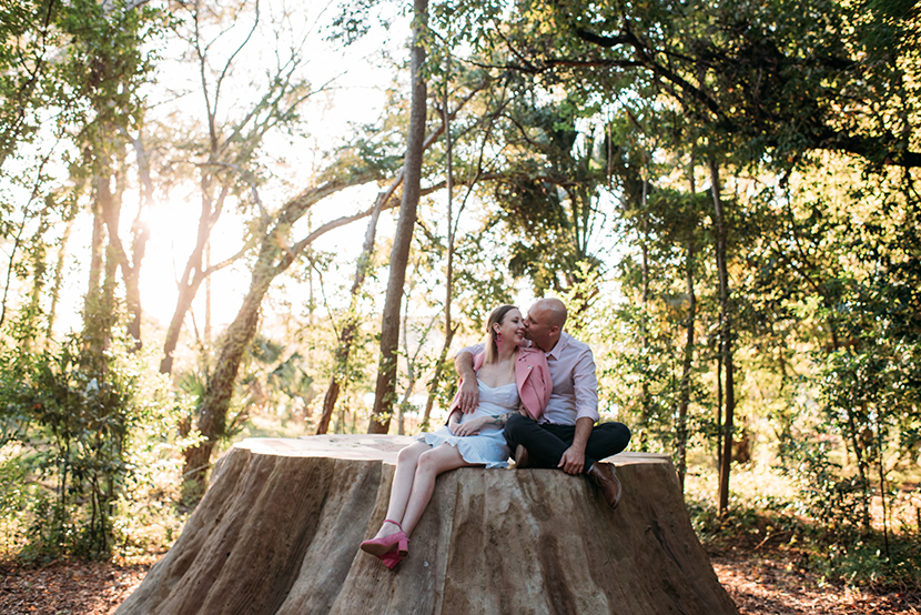 couple sitting on laguna gloria giant tree stump sculpture