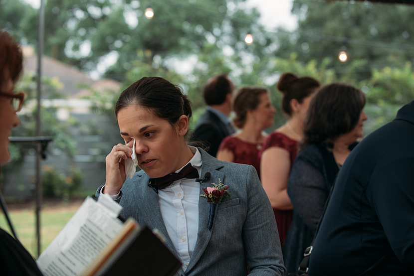 bride wipes her tears when seeing her beloved walk down the aisle