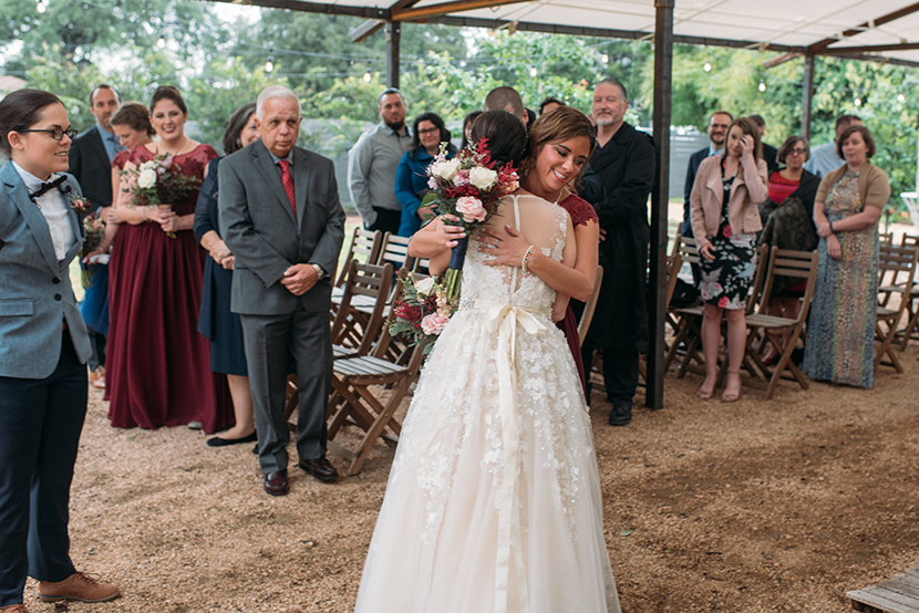 bride hugs her sister after walking down the aisle