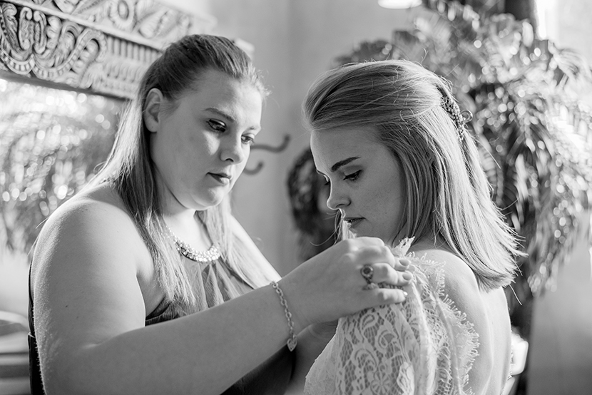 bridesmaid helps bride with her lace dress