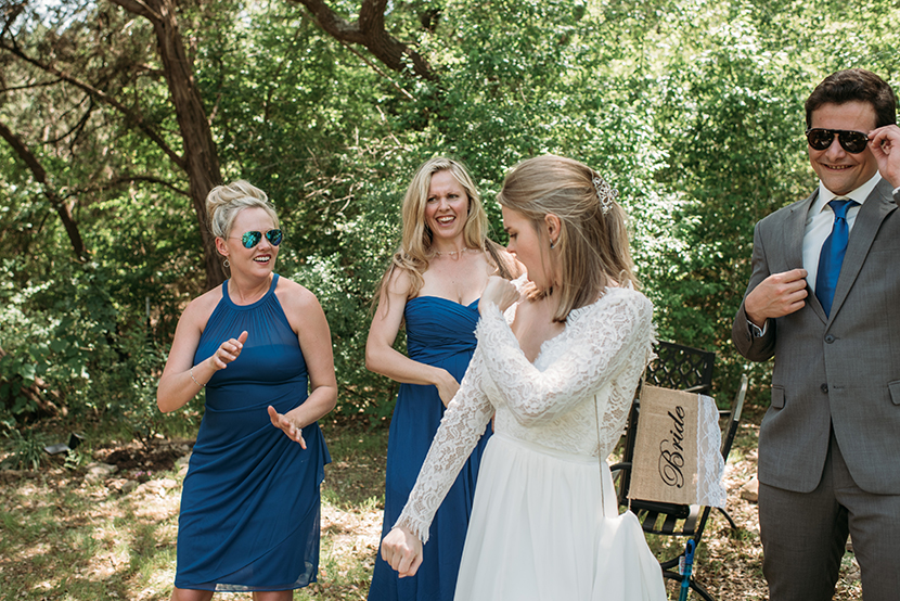bride dances with sisters in backyard wedding