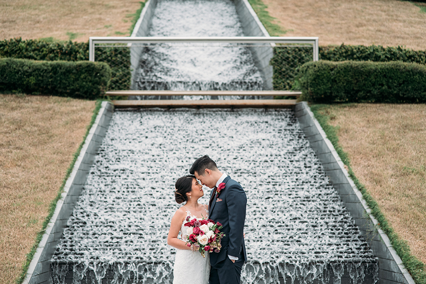 couple embraces in front of the water wall at mcgovern centennial gardens