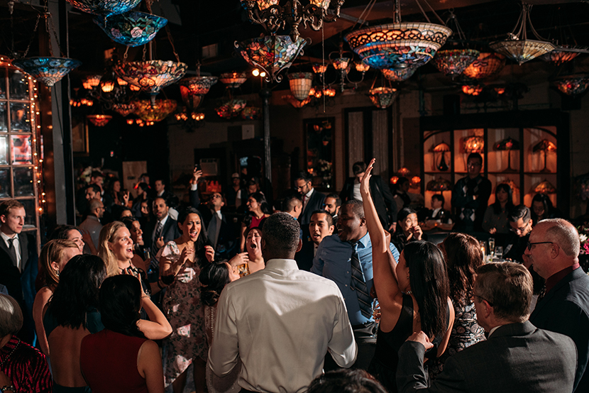 crowd dancing in a dark art bar wedding